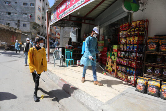 Palestinian workers spray disinfectant as a preventive measure amid fears of the spread of the coronavirus, in Dair Al Balah in the center of Gaza Strip, on April 4, 2020. (Photo: Ashraf Amra/APA Images)