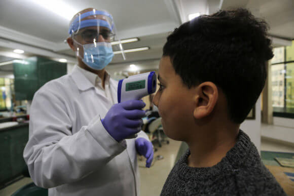 A Palestinian doctor wearing a face shield conducts a medical examination for a patient suspected of having COVID-19 in Gaza City on March 10, 2020. (Photo: Ashraf Amra/APA Images)