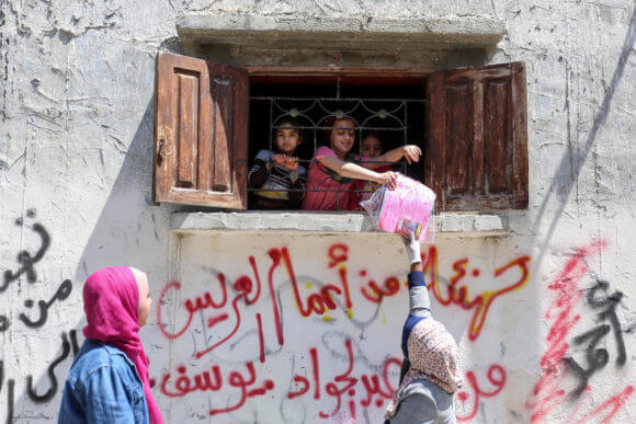Palestinian activists and volunteers from the Women's Program Center distribute crafts and reading material to children confined at home due to the novel coronavirus pandemic, in the Deir al-Balah refugee camp in the Gaza Strip, on April 13, 2020. (Photo: Ashraf Amra)