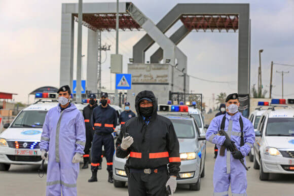 Members of Hamas security forces wear protective gear as a precaution against the coronavirus, at Rafah border crossing with Egypt in the southern Gaza Strip on April 14, 2020. (Photo: Ashraf Amra/APA Images)