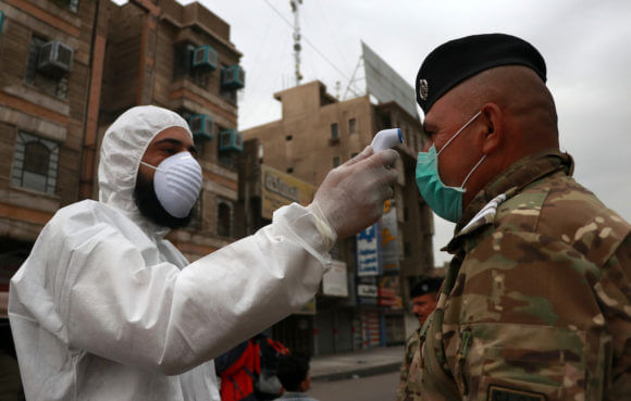 A Iraqi doctor uses a thermometer for a medical examination in Baghdad, Iraq, on March 20, 2020. (Photo: Anas Jomaa/APA Images)