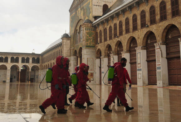 Syrian workers disinfect the Great Umayyad Mosque as a preventive measure amid fears of the spread of the coronavirus, in Damascus, Syria, on March 21, 2020. (Photo: Omar Estwani/APA Images)