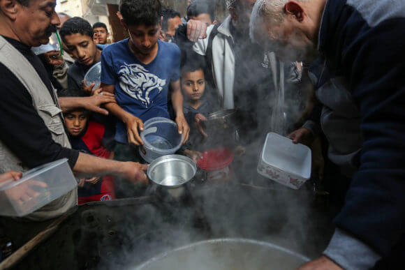 A Palestinian man distributes free food during the holy fasting month of Ramadan. (Photo: Ashraf Amra/APA Images)