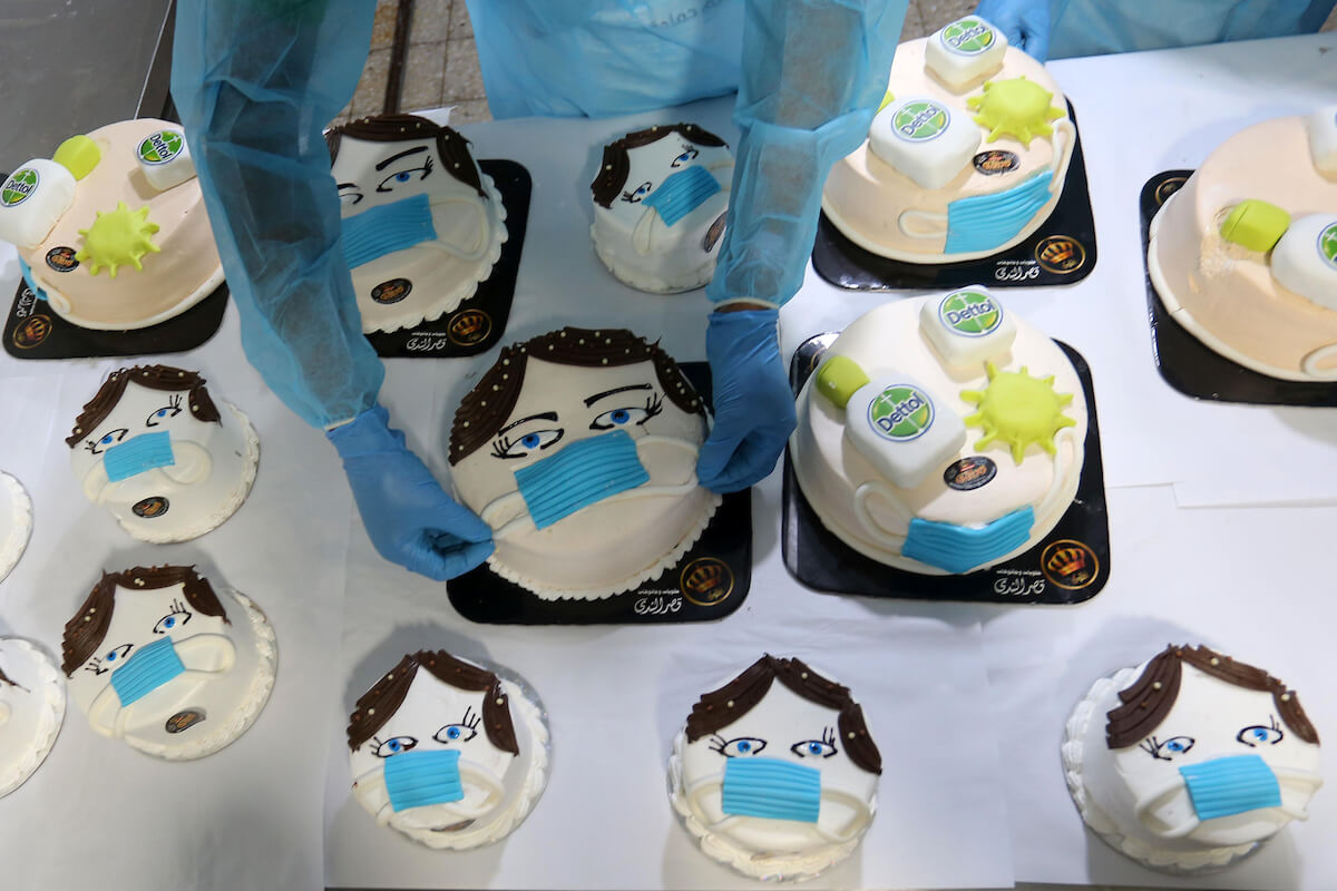 Palestinians put final touches on cakes that portrays a woman wearing a face mask with model of bottel of Dettol, a sterilizing soap, at their shop in Khan Yunis in the southern Gaza Strip on March 31, 2020. (Photo: Ashraf Amra/APA Images)