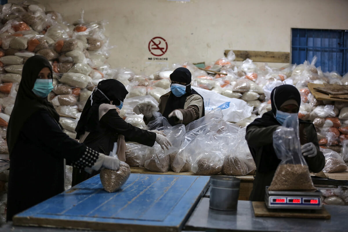 Palestinian employees at the United Nations Relief and Works Agency for Palestinian Refugees, or UNRWA, wear protective masks and gloves as they prepare food aid rations for delivery to refugee homes. Picks at UN centers were canceled as a measure to prevent the spread of the coronavirus, in Dair Al Balah in the Gaza strip, on March 31, 2020. (Photo: Ashraf Amra/APA Images)