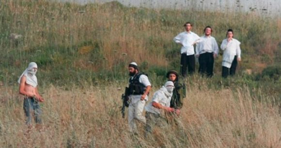 Armed and masked Israeli settlers harassing Palestinians. Published by IMEMC in April 2020, but photo is undated.