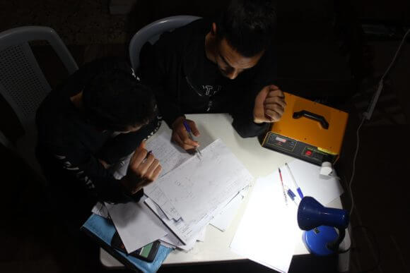Palestinians use a SunBox to light a lamp in their home. (Photo: SunBox)