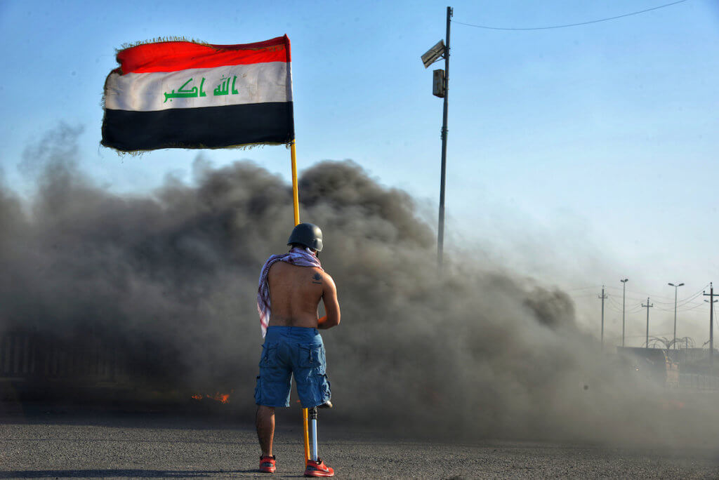 An Iraqi protester holds flag as he takes part in an anti-government demonstration in Iraq's southern city of Nasiriyah in Dhi Qar province on March 1, 2020. (Photo: Wadaa al-Aumry/APA Images)