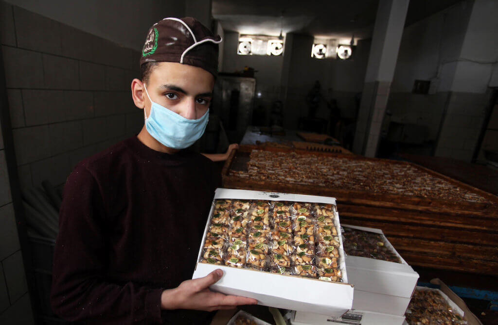 """Palestinians prepare sweet known in Arabic as """"Halkoum"""" to be sold ahead of the Eid al-Fitr holiday, at a factory in Gaza city on May 14, 2020. Photo by Mahmoud Ajjour"""
