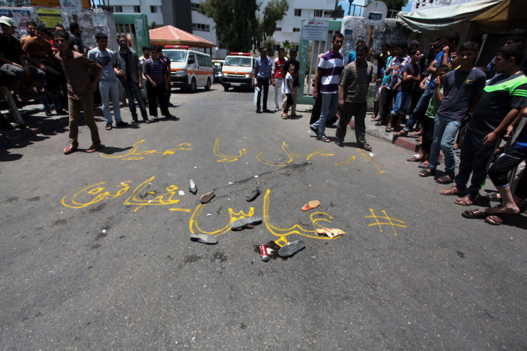 "Palestinians walk next to a write on the ground that reads ""Abbas is a traitor"" during a protest against the Palestinian President Mahmoud Abbas outside al-Shifa hospital in Gaza City on July 15, 2014. (Photo: Ashraf Amra/APA Images)"