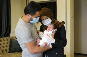 Alaa and Tasneem al-Batat, who both recovered from COVID-19, hold their new born baby Tayem inside their house in al-Dahriya village, south in the West Bank City of Hebron on May 17, 2020. The parents were receiving treatment for coronavirus when the mother was rushed to give birth. (Photo: Mosab Shawer/APA Images)