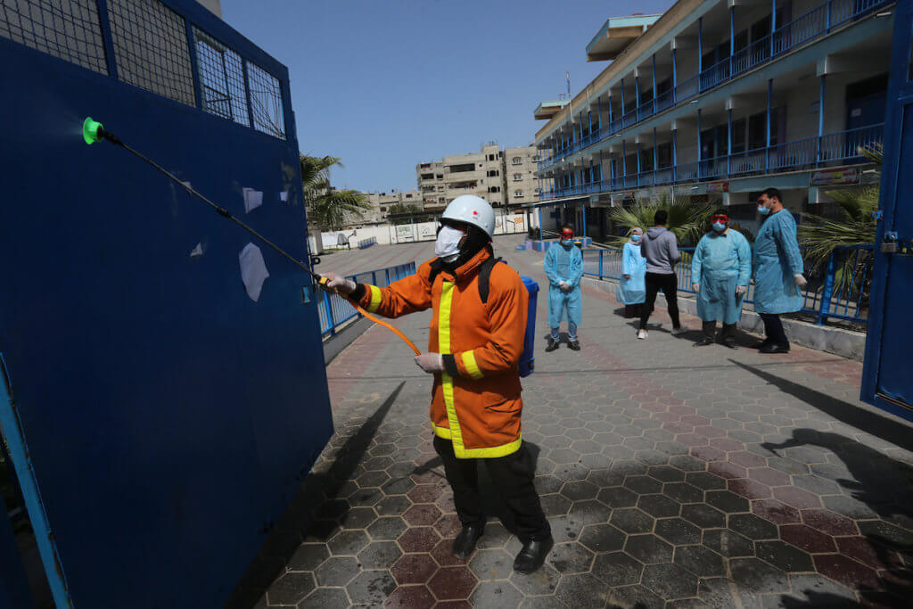 Palestinian Members of the Civil Defense disinfect the streets as a preventive measure amid fears of the spread of the coronavirus, in Khan Yunis in the southern of Gaza Strip, on March 23, 2020. (Photo: Ashraf Amra/APA Images)