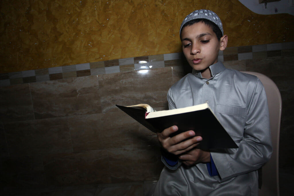 A Palestinian family reads from the Quran during a night prayer known as ''Tarawih'' in their home after mosques are closed in measures to stem the spread of the coronavirus, in Gaza City on April 24, 2020. (Photo: Mahmoud Ajjour/APA Images)