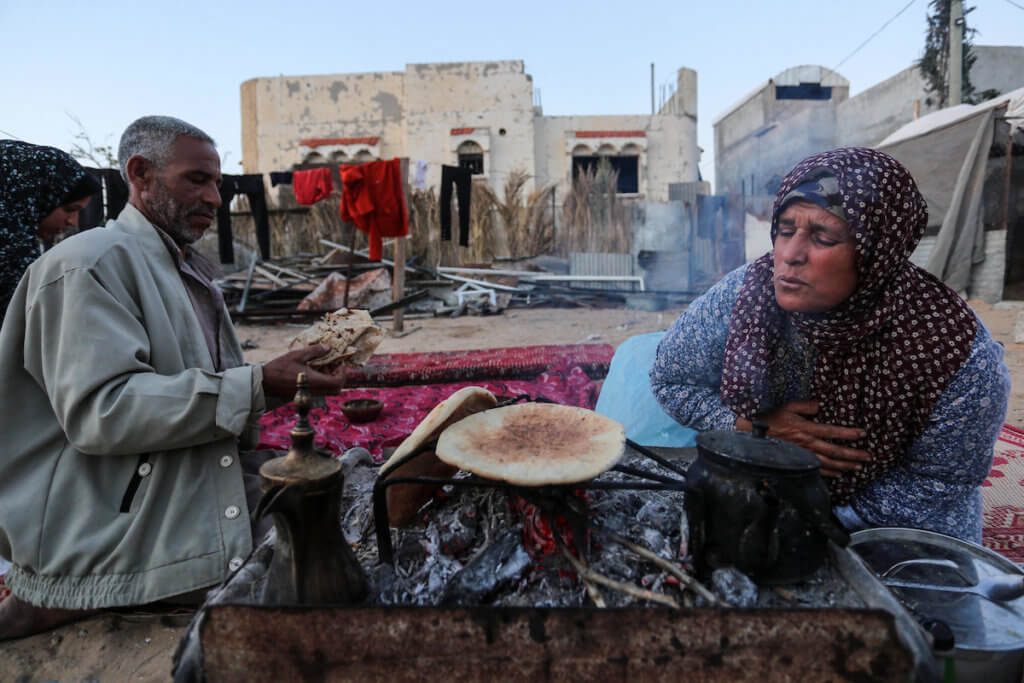 A Palestinian family breaks their fast at the site of their destroyed house in Khan Yunis southern in Gaza City on April 26, 2020. (Photo: Ashraf Amra/APA Images)