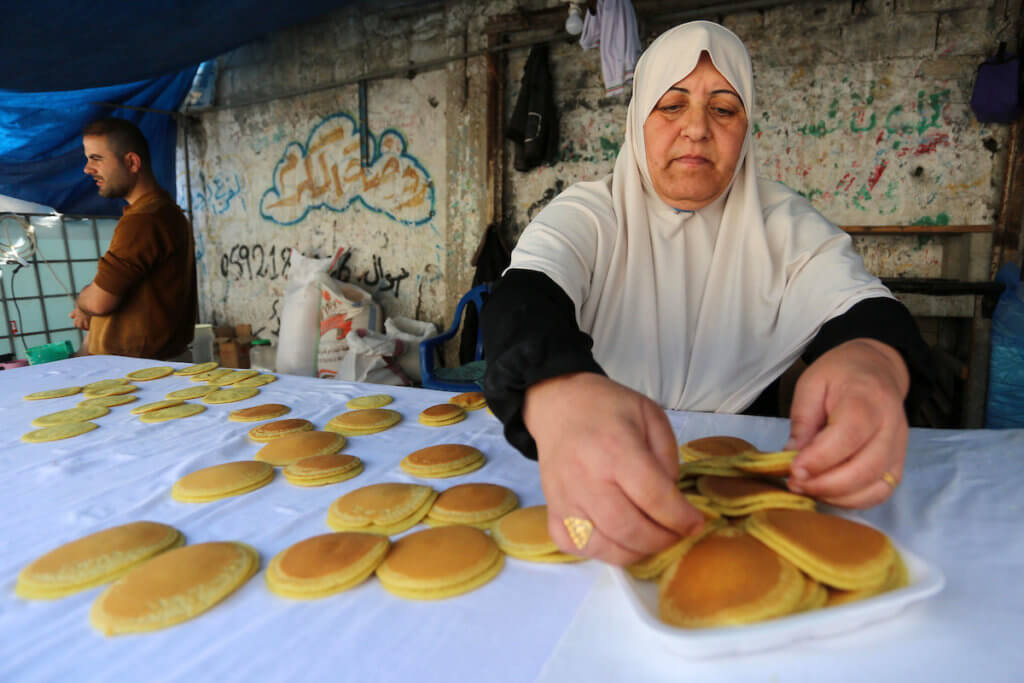 Um Iyad, 55, prepares qatayef, a traditional sweet pancake popular during the Ramadan holiday, in Deir al-Balah in the center of the Gaza Strip on April 27, 2020. (Photo: Ashraf Amra/APA Images)