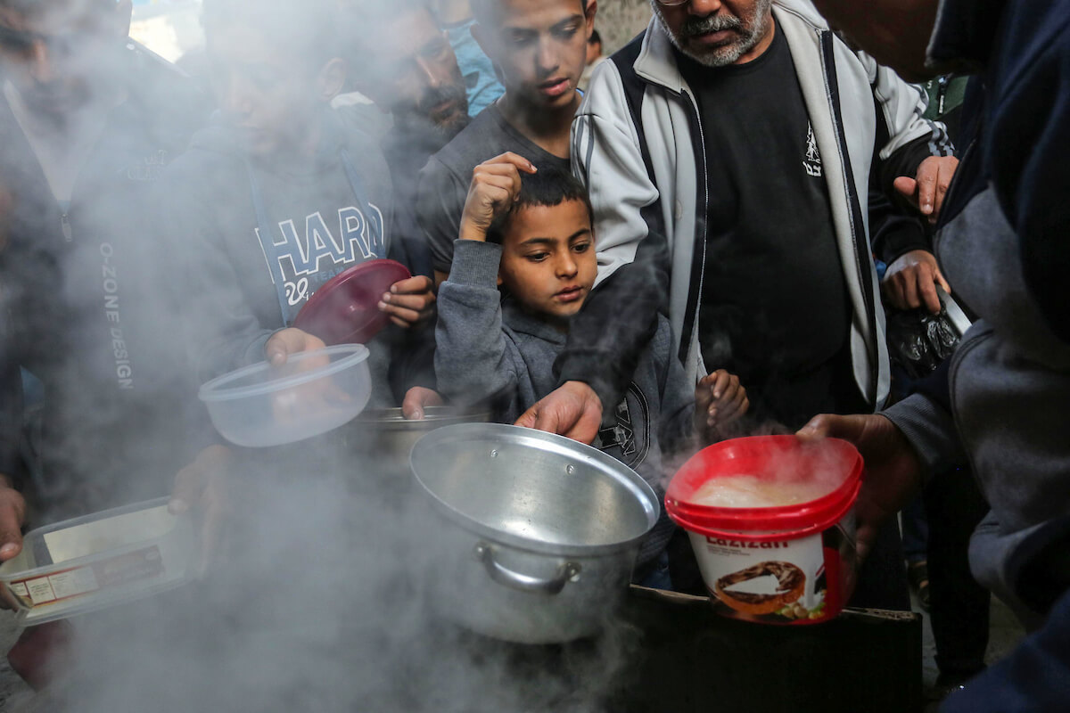 A Palestinian man distributes free food during the holy month of Ramadan in Shuja'iyya neighborhood in Gaza City on April 28, 2020. Muslims around the world celebrate the month of Ramadan by praying during the night time and abstaining from eating and drinking during the period between sunrise and sunset. (Photo: Ashraf Amra/APA Images)