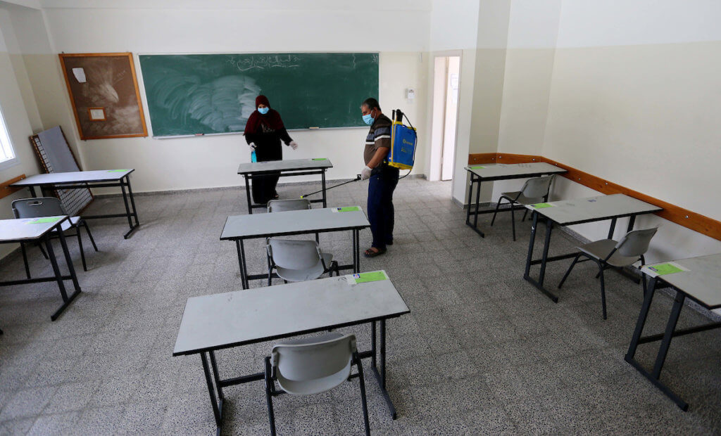 "Palestinian workers disinfect a school for the final high school exams, known as ""Tawjihi"", as a preventive measure amid fears of the spread of the novel coronavirus, in Nuseirat refugee camp in the center of Gaza Strip on May 28, 2020. (Photo: Ashraf Amra/APA Images)"