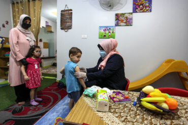 Palestinian Kindergarten teacher wearing a face mask and gloves, play with children after the decision to open schools across the Gaza Strip, in Gaza City, on June 2, 2020. (Photo: Mahmoud Ajjour/APA Images)