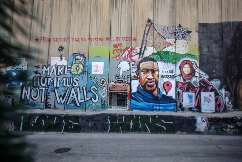 A mural depicts George Floyd, a black American who died after a white policeman knelt on his neck during an arrest in the U.S., at the Israeli separation wall in the West Bank city of Bethlehem on June 9, 2020. (Photo: Abedalrahman Hassan/APA Images)