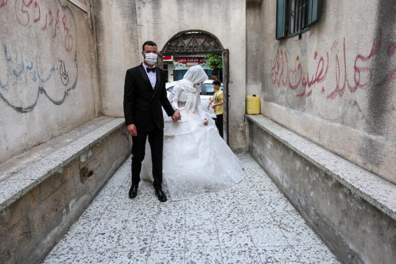 A Palestinian bride and groom wearing masks as a precaution against the spread of COVID-19, during their wedding ceremony in Khan Younis in the southern of Gaza strip on June 11, 2020. (Photo: Ashraf Amra/APA Images)