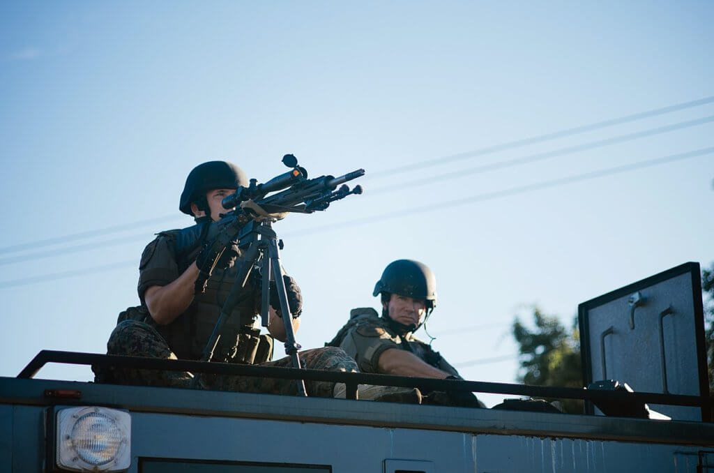 Sharpshooter, with weapon trained, atop a SWAT vehicle during the protests in Ferguson, MO following the police killing of Michael Brown, August 2014 (Photo: Jamelle Bouie/Wikimedia)