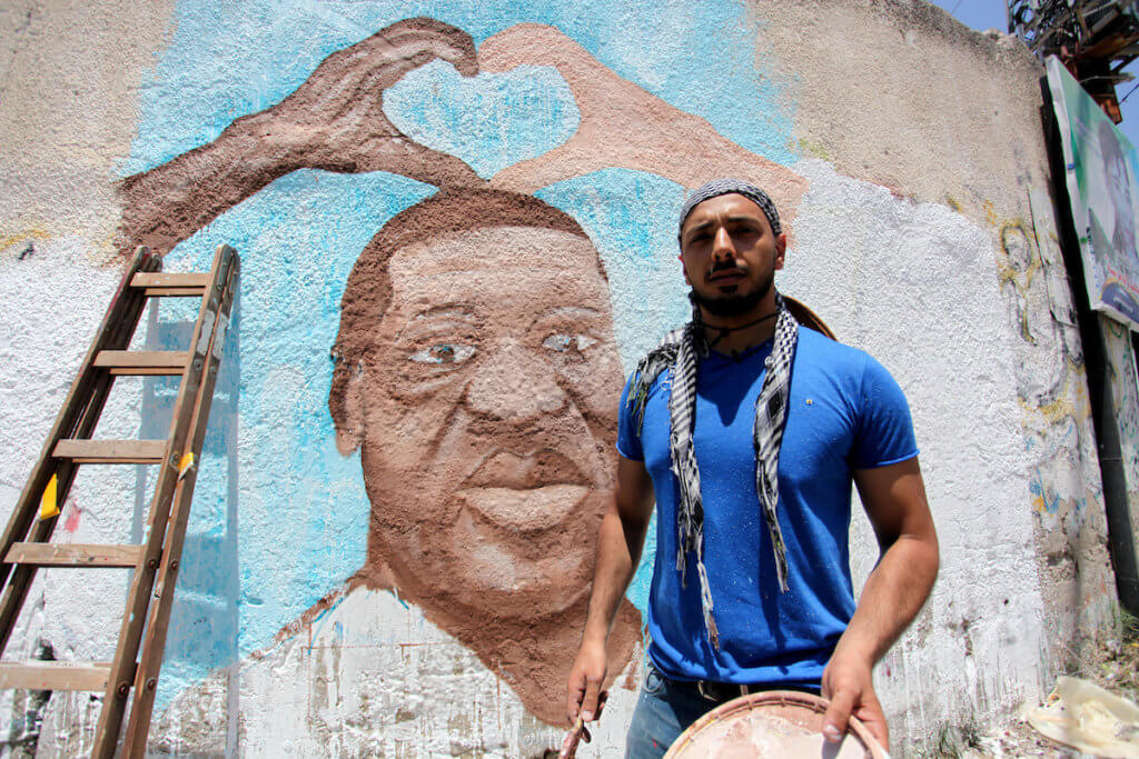 Palestinian artist paints a mural for George Floyd, a black American who died after a white policeman knelt on his neck during an arrest in the U.S., in Gaza City on June 16, 2020. (Photo: Mahmoud Ajjour/APA Images)