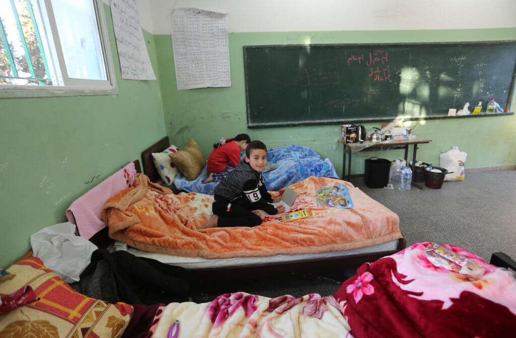 Palestinian children quarantined in a government isolation center at a school sit on beds in Deir al-Balah in the center of Gaza Strip, March 21, 2020. (Photo: Ashraf Amra/APA Images)