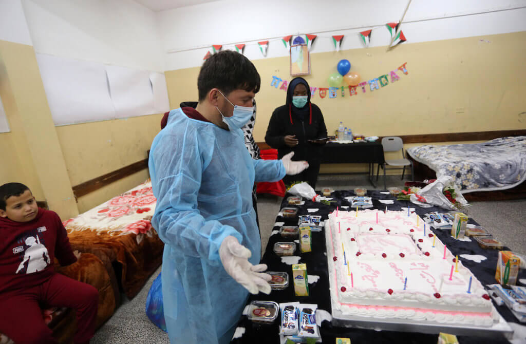 Palestinians quarantined in a school operating as a government isolation center celebrate on Mother's Day in Deir al-Balah in the center of Gaza Strip March 21, 2020. (Photo: Ashraf Amra/APA Images)