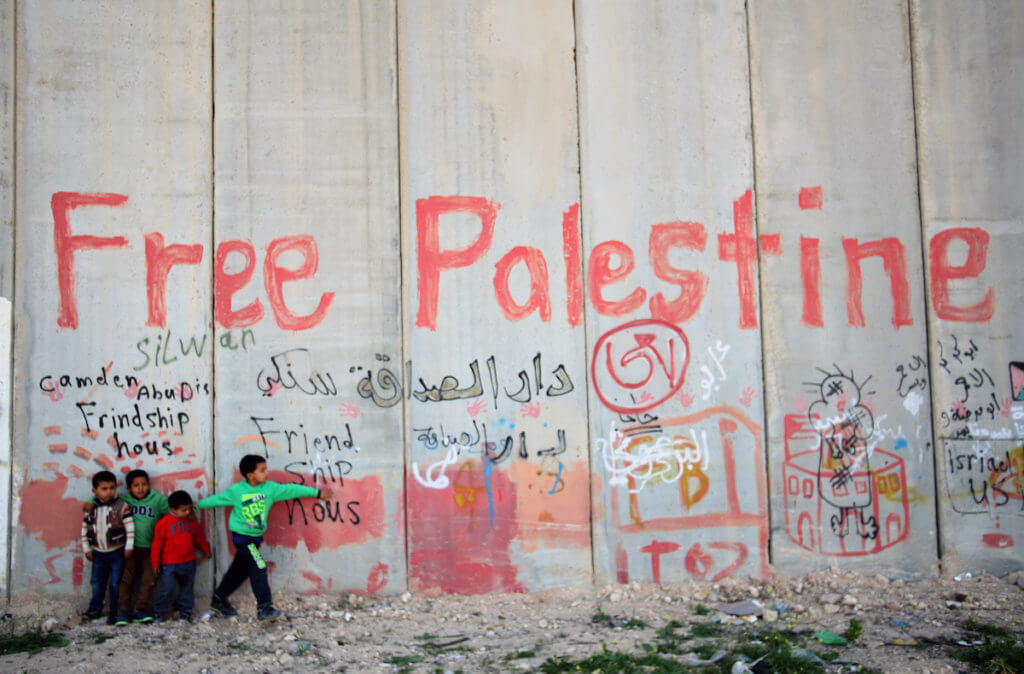 Palestinian children stand in front of Israeli separation barrier in the east Jerusalem village of Abu Dis, April 3, 2014. (Photo: Saeed Qaq/APA Images)