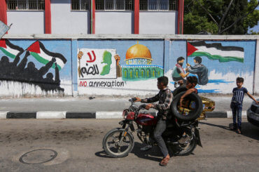 Palestinians ride past a mural protesting Israel's West Bank annexation plans, in Rafah in the southern Gaza Strip, on July 1, 2020. (Photo: Ashraf Amra/APA Images)