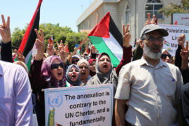 Palestinians hold placards and national flags during a demonstration against Israel's West Bank annexation plans in Gaza City on July 1, 2020. Israel's Prime Minister Benjamin Netanyahu, emboldened by the US Mideast plan released in January, has vowed to annex the Jordan Valley in addition to 135 settlements that are already considered illegal by the international community an estimated 30% of the occupied West Bank. (Photo: Ashraf Amra/APA Images)