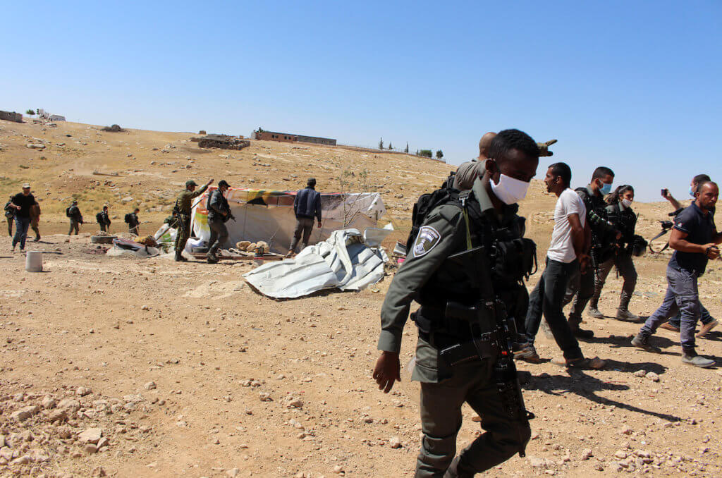 Israeli forces stand by Palestinians homes demolished south of the Yatta village in the southern West bank district of Hebron on June 3, 2020. (Photo: Mosab Shawer/APA Images)