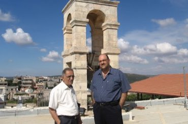 Attorney Sabri Jiryis (L) and Sam Bahour standing on the rooftop of the 113-year-old Saint Elias Church in the Palestinian village of Fassouta in the Western Galilee. The South Lebanon skyline is in the background.