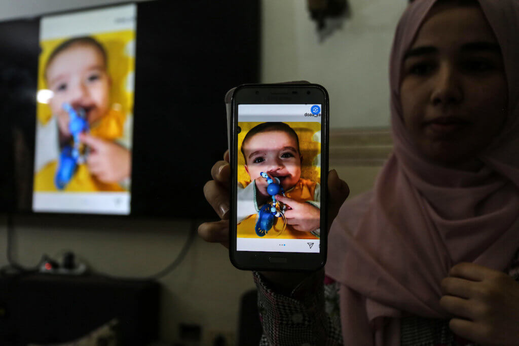 A relative of nine-months-old Omar Yagi displays a picture of the Palestinian baby who died after he was unable to exit Gaza for a live-saving heart surgery. Palestinian officials cut coordination for exit permits with Israel in late May. (Photo: Ashraf Amra/APA Images)