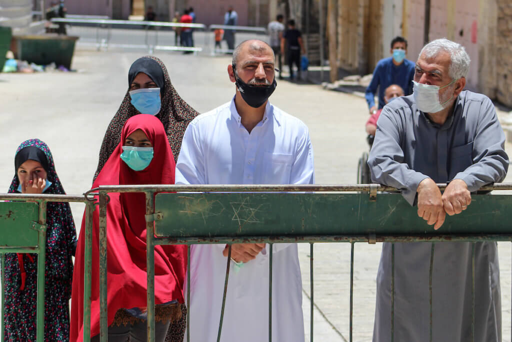 Israeli soldiers stands guard as Palestinians wearing face masks enter the Ibrahimi Mosque to perform Friday prayers in the midst of the coronavirus pandemic in the West Bank city of Hebron on June 26, 2020. (Photo: Mosab Shawer/APA Images)