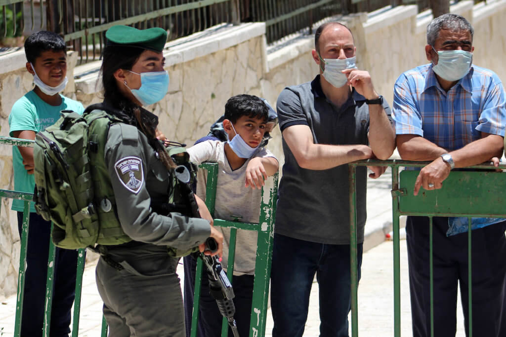 A member of the Israeli security forces stands guard as Palestinians wearing face masks enter the Ibrahimi mosque, to perform the Friday prayer, in the midst of the coronavirus COVID-19 outbreak, in the West Bank town of Hebron on June 26, 2020. (Photo: Mosab Shawer/APA Images)