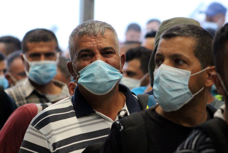 Palestinian laborers wearing masks queue to enter Israel through the Mitar checkpoint in the West Bank city of Hebron on June 28, 2020. (Photo: Mosab Shawer/APA Images)
