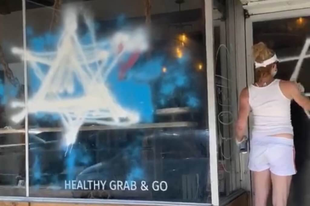 A member of the JDL defacing the Foodbenders storefront (Photo: Twitter)