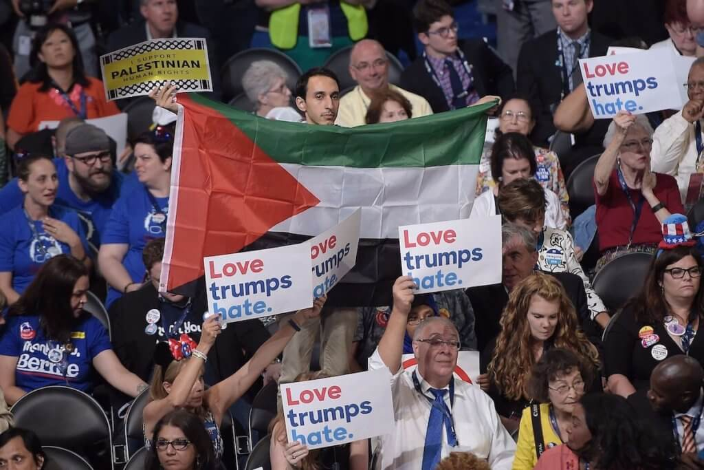 A man displays a Palestinian flag amidst delegates holding up signs on Day 1 of the Democratic National Convention at the Wells Fargo Center in Philadelphia, Pennsylvania, July 25, 2016. (Photo: BRENDAN SMIALOWSKI/AFP/Getty Images)