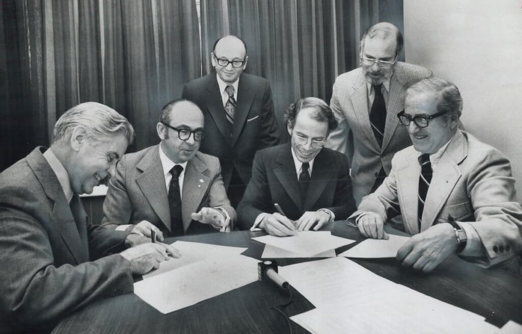 Leaders of the United Church of Canada and B'nai B'rith sign a statement regretting their dispute over the treatment of Palestinian refugees. Signers (from left) are Rev. George M. Morrison; United Church; Sydney Maislin; B'nai B'rith; Rt. Rev. N. Bruce McLeod; United Church; and Herbert S. Levy; B'nai B'rith. Witnessing the signatures yesterday are Louis Ronson (left) and Morley S. Wolfe. (Photo: Toronto Star Archives via Toronto Public Library)