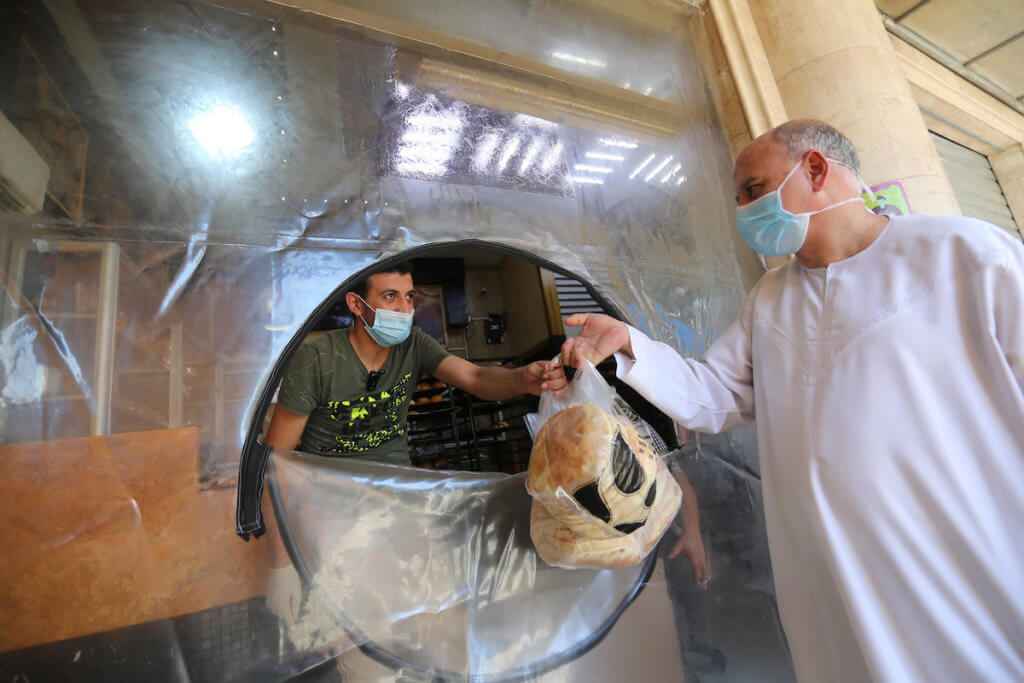 Palestinian workers wear facemasks during a 48 hour lockdown imposed following the discovery of the first coronavirus cases outside of quarantine in the Gaza Strip, August 25, 2020. (Photo: Ashraf Amra/APA Images)