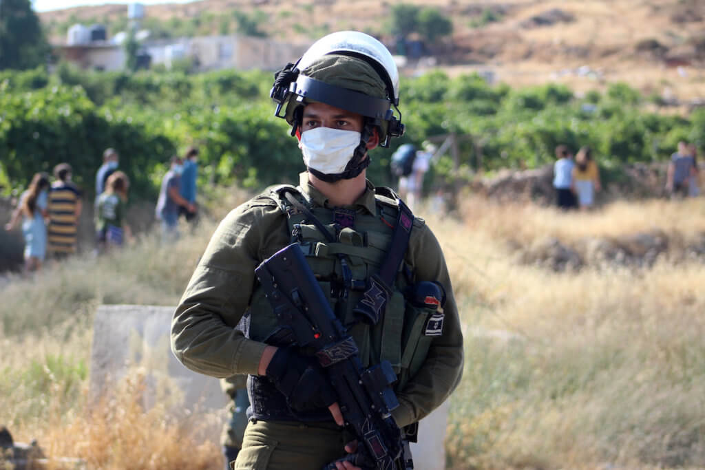 """Israeli security forces stand guard as settlers gather on """"Mount Jumjumah"""" in the city of Halhul, north of the West Bank of Hebron on June 30, 2020. (Photo: Mosab Shawer/APA Images)"""