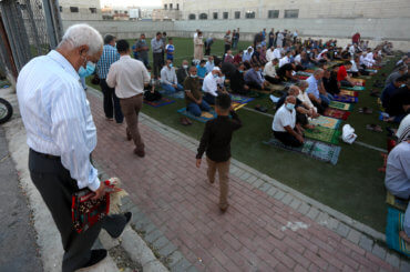 Palestinian Muslims wearing masks perform prayers for Eid al-Adha or the Feast of the Sacrifice, near Salfit in the Israeli-occupied West Bank on July 31, 2020. (Photo: Shadi Jarar'ah/APA Images)