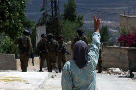 A Palestinian woman flashes a victory sign as she shouts at Israeli forces following a protest against the expropriation of Palestinian land on July 19, 2013 in the village of Kfar Qaddum, near the occupied West Bank city of Nablus. (Photo: Nedal Eshtayah/ APA Images)