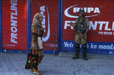 A security personnel stands guard as a Kashmiri woman walks past in front of closed shops in Srinagar on August 23, 2019. (Photo: Tauseef Mustafa/AFP/Getty Images)