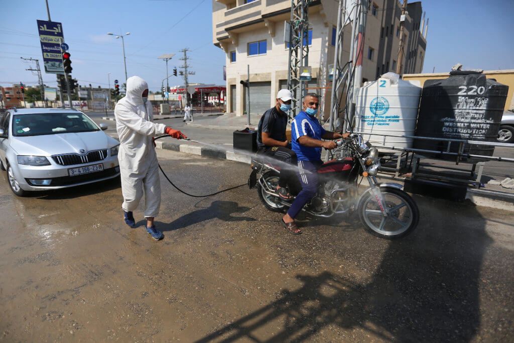 Palestinian health workers spray disinfectant on vehicles entering the Maghazi refugee camp as a precaution against the spread of the coronavirus in the central Gaza Strip on September 1, 2020. (Photo: Ashraf Amra/APA Images)