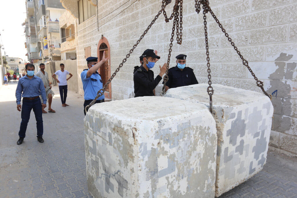Palestinian police officers close a road with concrete barriers during a lockdown following the outbreak of the coronavirus, in Deir Al Balah in the central of Gaza Strip, on September 3, 2020. (Photo: Ashraf Amra/APA Images)