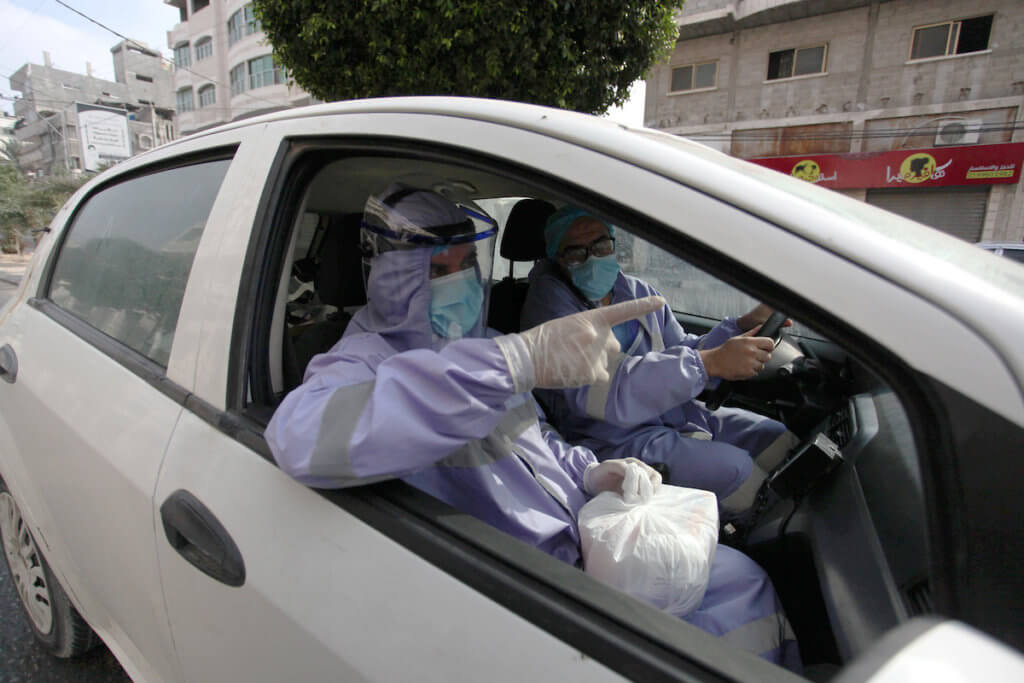 Palestinian nurses from the United Nations Relief and Works Agency for Palestinian Refugees wear protective gear as they distribute monthly medications for chronic illnesses in Gaza City on September 3, 2020. (Photo: Mahmoud Ajjour/APA Images)
