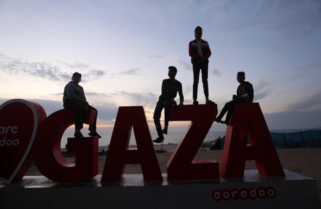 Palestinians youth sit at the beach during sunset in Gaza city on April 15, 2020. (Photo: Ashraf Amra/APA Images)