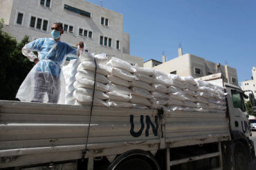 UNRWA employees wearing protective masks and gloves, transport food aid to refugee family homes, amid the coronavirus disease (COVID-19), in Gaza City, on September 15, 2020. (Photo: Mahmoud Ajjour/APA Images)